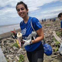 Beach clean up volunteer with plastic